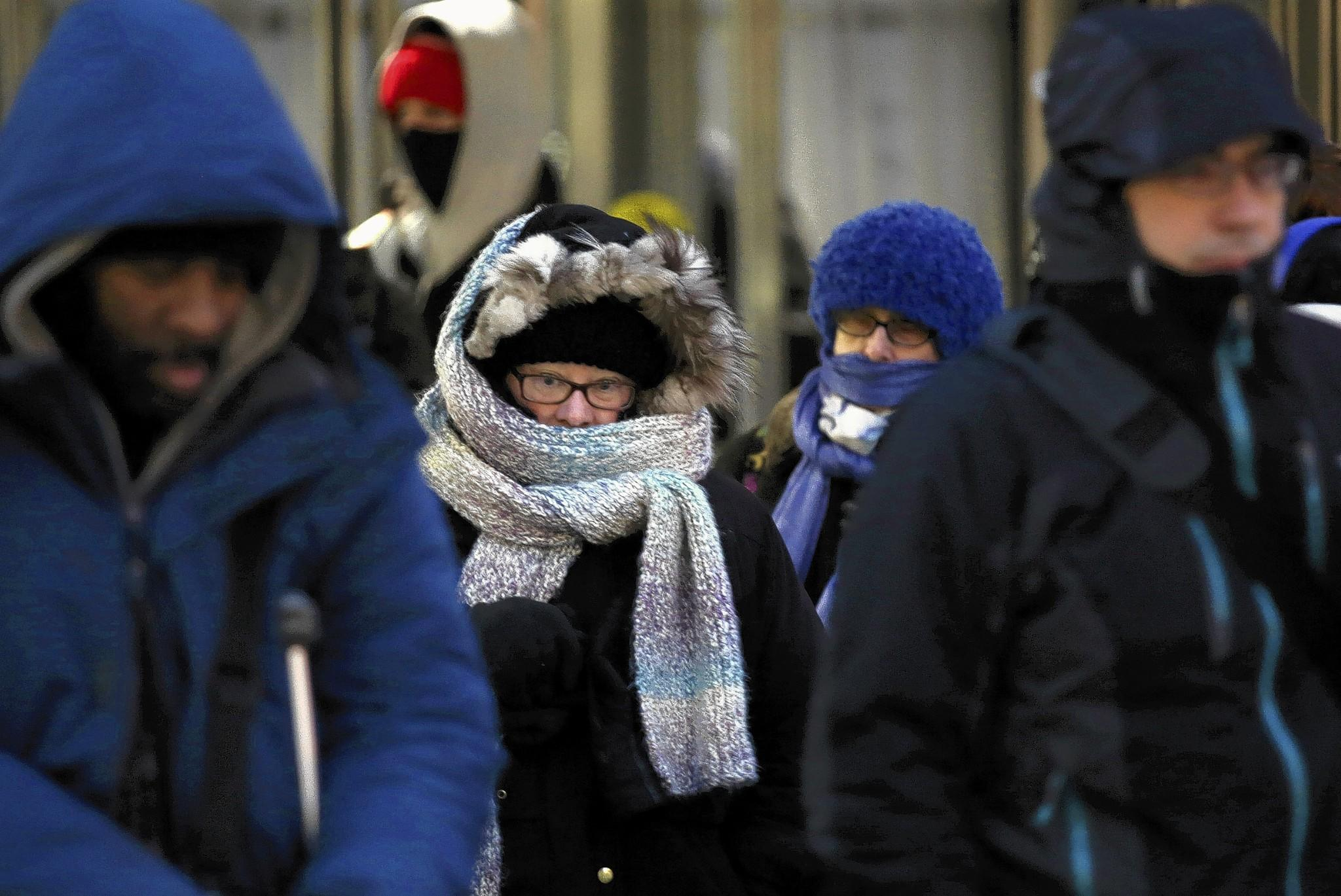 Commuters show off their scarf-wrapping techniques as they brace themselves to exit Union Station in downtown Chicago on Monday.