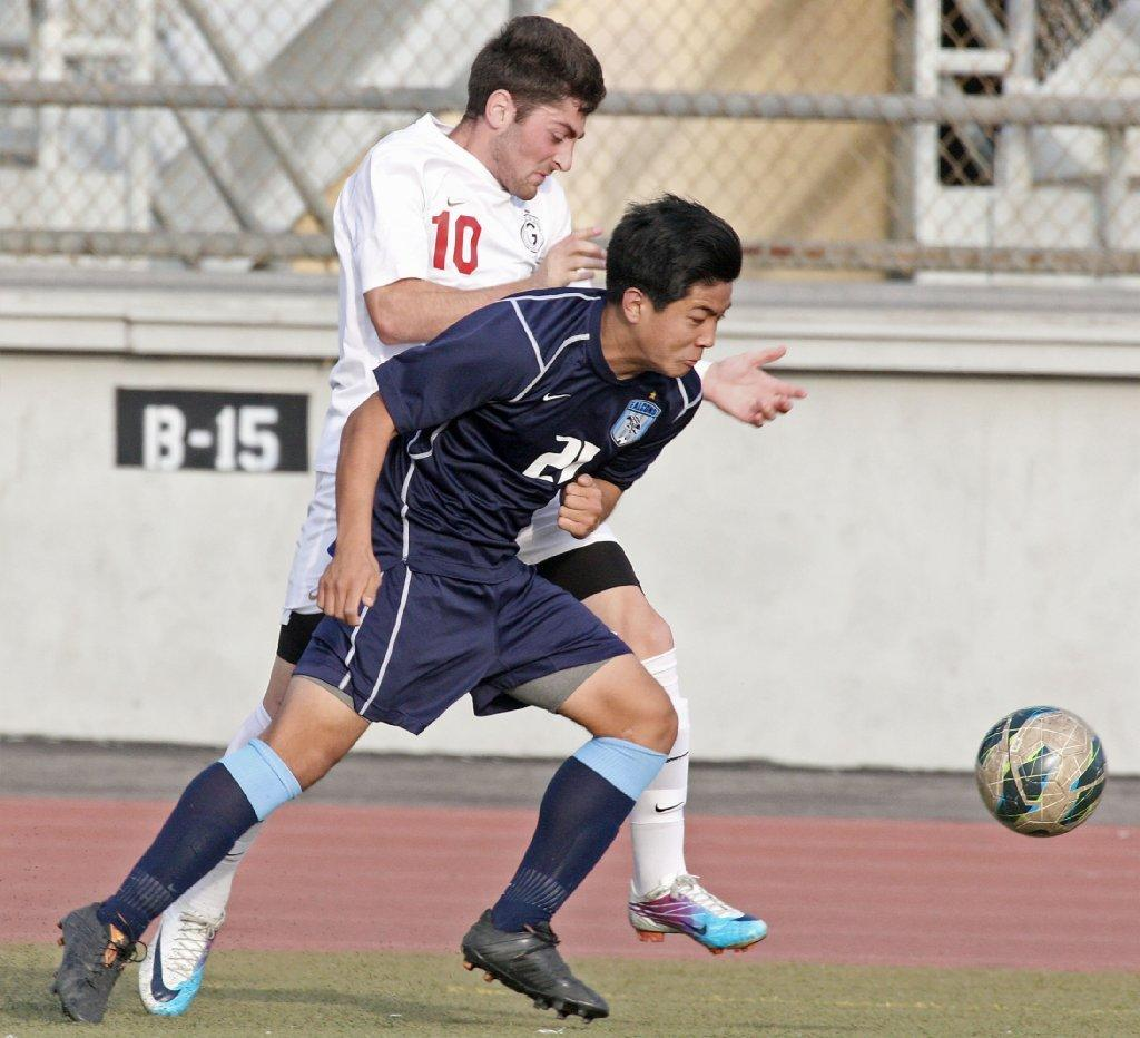 Glendale High boys' soccer player Avo Haroutunyan and Crescenta Valley's Augustine Ahn chase after a ball during a Pacific League match at Glendale High on Tuesday. The Falcons won, 3-2. (Roger Wilson/Staff Photographer)
