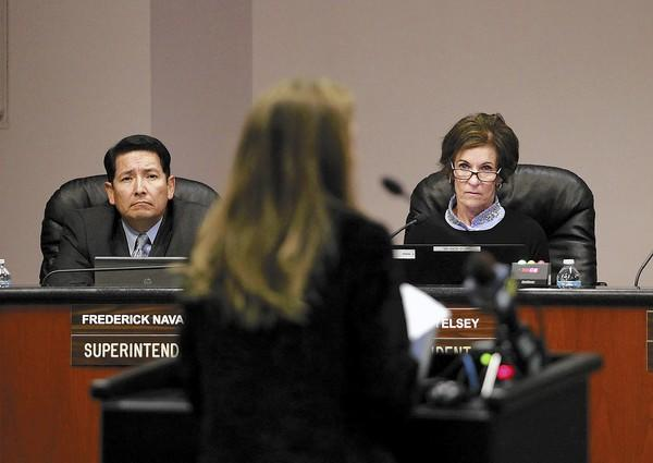 Superintendent Frederick Navarro, left, and President Karen Yelsey listen to a woman's concerns over the recent Corona Del Mar High school cheating scandal during Newport-Mesa Unified School District board meeting on Tuesday.