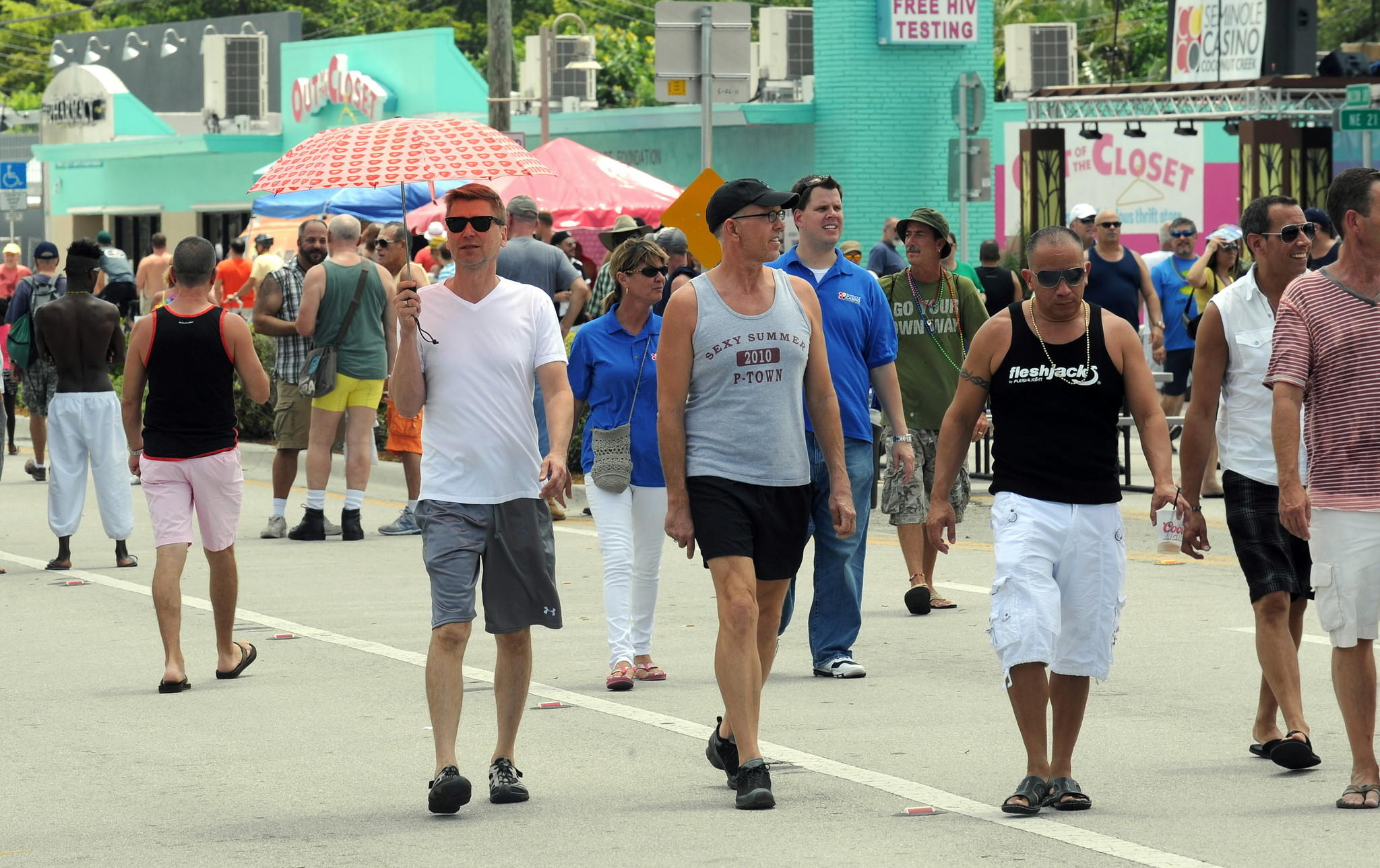 Mark Hagen catches a little shade from his umbrella while enjoying the Stonewall Festival in downtown Wilton Manors in June 2013. Jim Rassol, Sun Sentinel