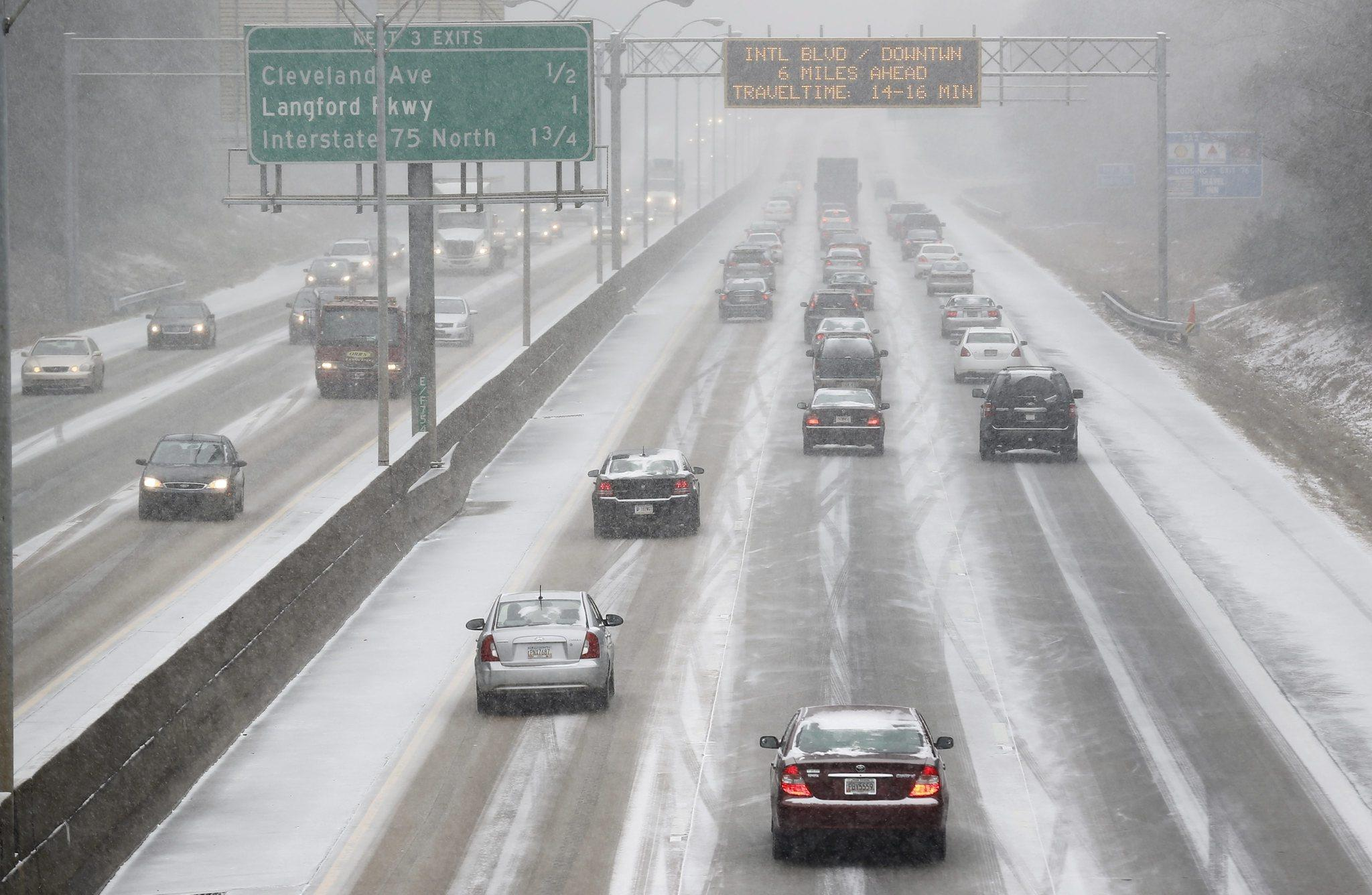 Commuters drive in the snow on Interstate 85 as a winter storm affects Atlanta.