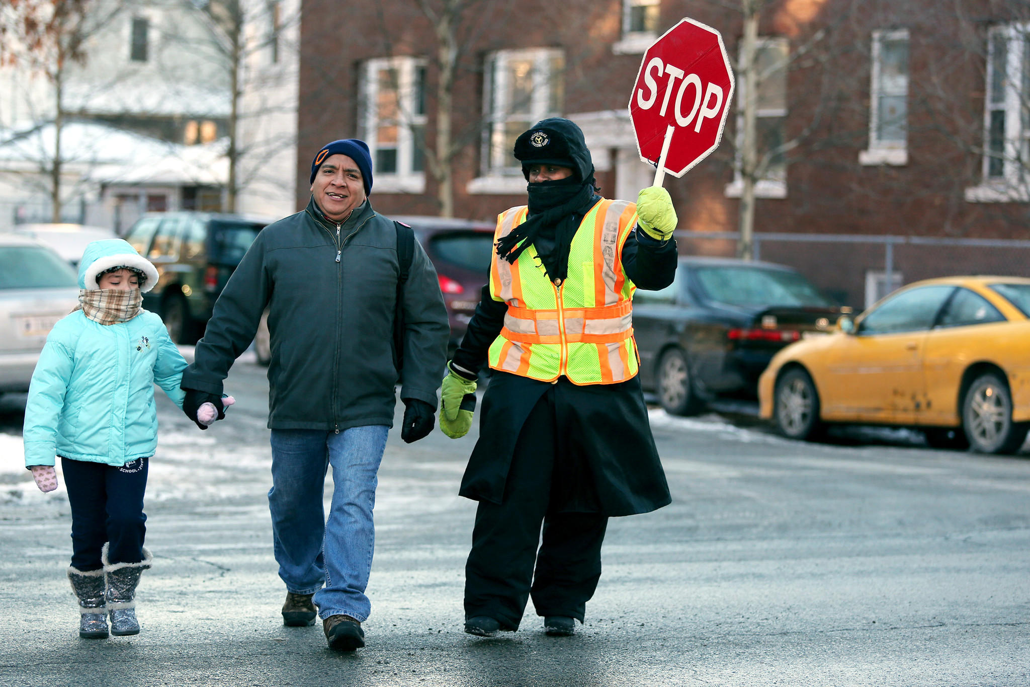 Crossing guard Tina Dockery helps a man and young girl cross the street on their way to school.