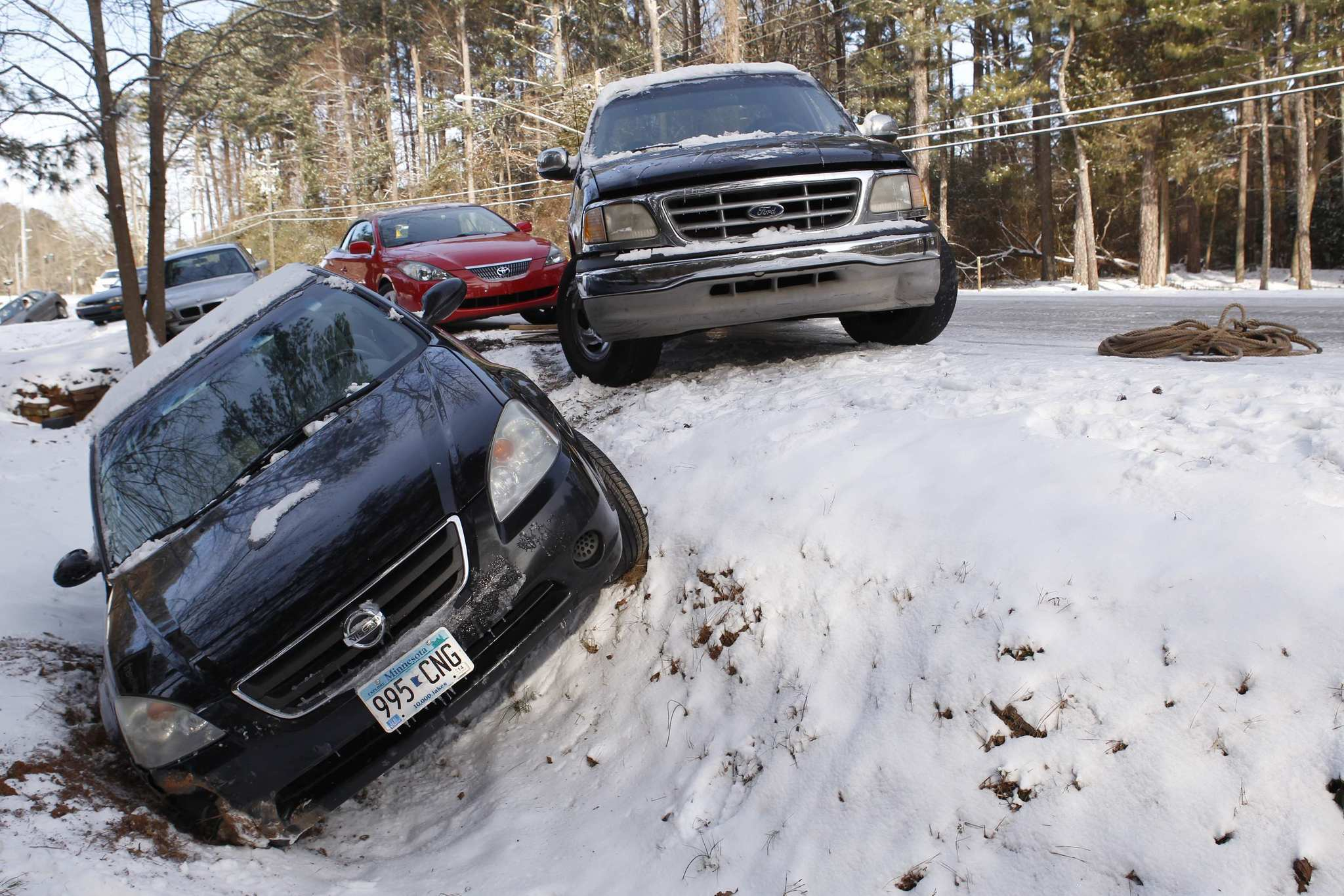 A car sits in a ditch along with other abandoned cars after running off the roadway due to a snow storm in Atlanta, Georgia, January 29, 2014. A rare winter storm gripped the U.S. South on Wednesday, killing five people, stranding children overnight at their schools, gnarling traffic across many states and canceling flights at the world's busiest airport.