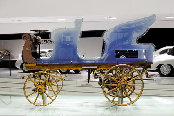 The unrestored P1 model on display in the Porsche Museum. The remaining chassis and drivetrain can be seen with a replica of the body work in blue showing what the original car would have looked like.