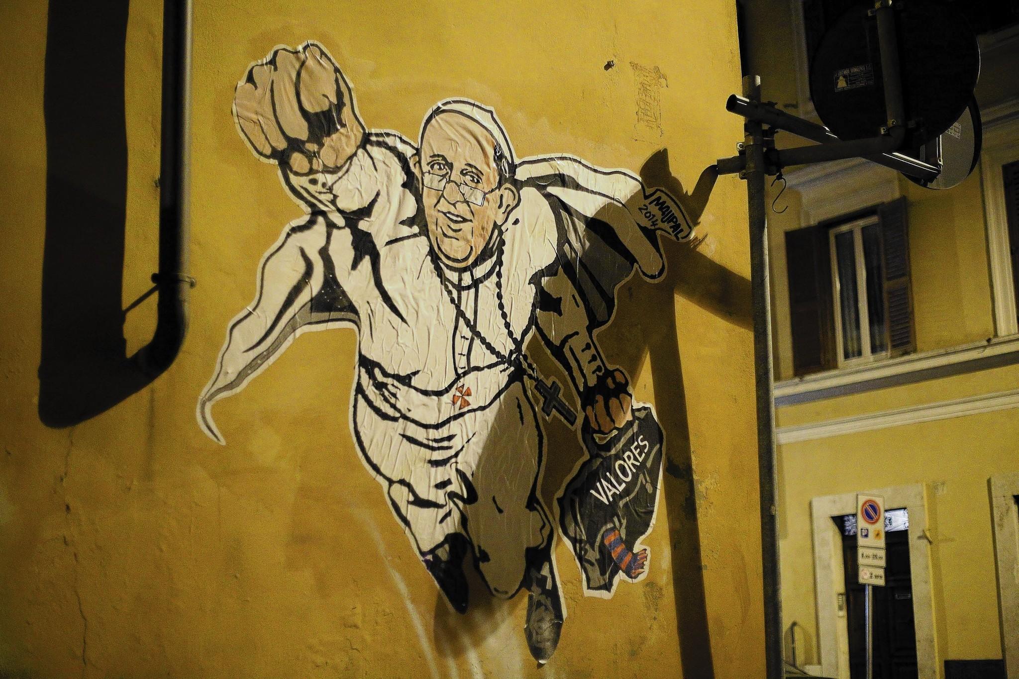 """Vista de un grafiti en el que aparece el papa Francisco representado con estética de superhéroe, hoy martes 28 de enero de 2014, en Roma, Italia. El papa aparece volando, como si de Superman se tratase, ataviado con la sotana blanca, el solideo y los zapatos negros por los que optó nada más ser elegido pontífice en lugar de los rojos clásicos, que representan la sangre de Cristo. Bergoglio sostiene con la mano izquierda su ya clásico maletín negro, en el que aparece escrita en español la palabra """"valores"""" y del que emerge un calcetín a rayas rojas y azules, los colores de San Lorenzo de Almagro, el equipo del que el papa es seguidor."""