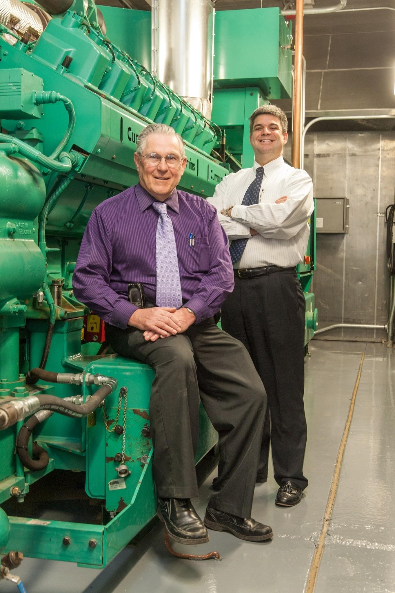 Wayne Rutty (left), project manager, and David Giuffrida, vice president of facilities and support services, beside the combined heat and power generator at Middlesex Hospital.