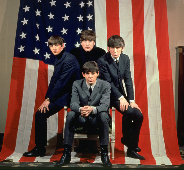 The Beatles, clockwise from top center, John Lennon, George Harrison, Paul McCartney and Ringo Starr, pose with an American flag in a Paris photo studio prior to their first visit to the United States in 1964.