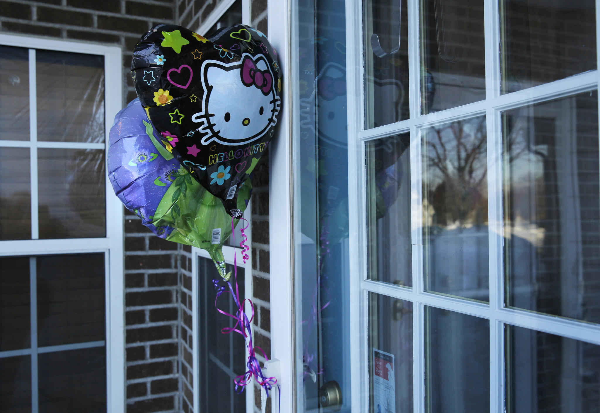 Balloons left by a well-wisher adorn the entrance to the Mundelein home where an 11-year-old girl was stabbed to death.