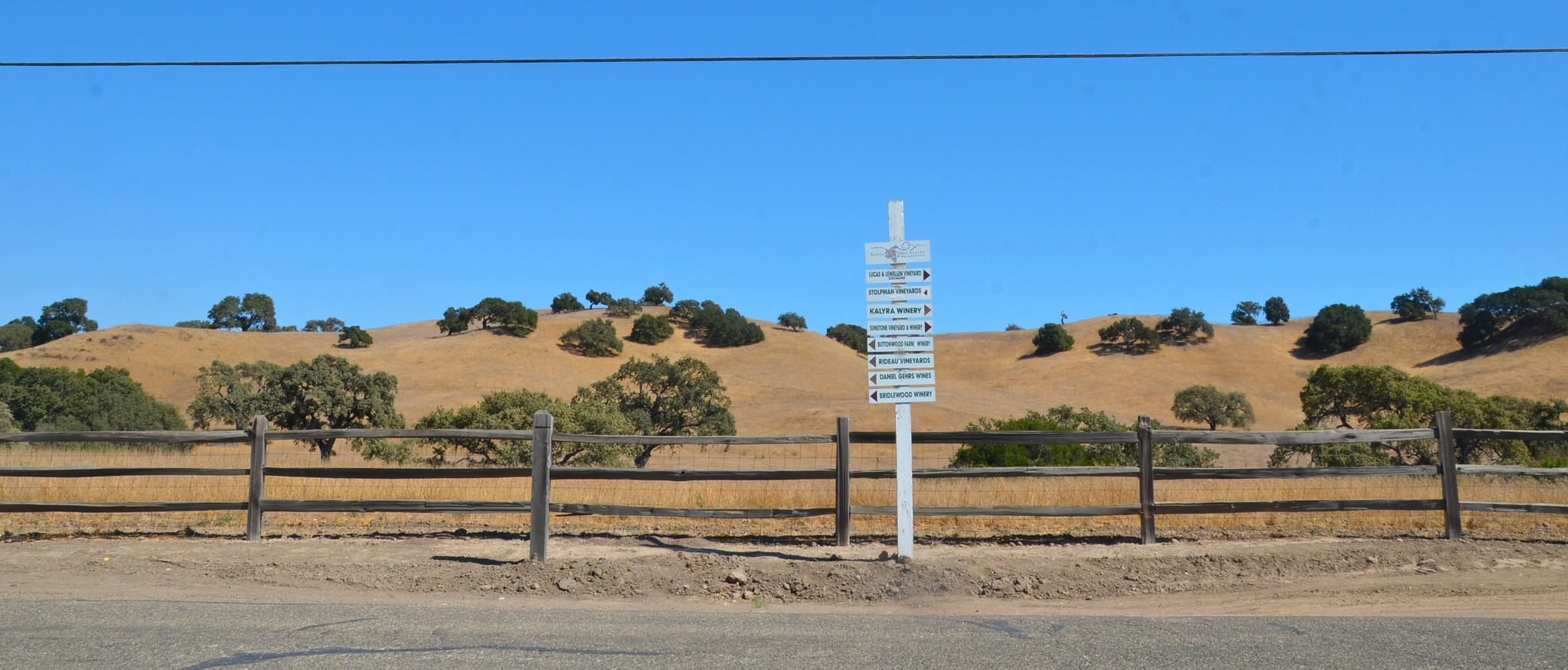 The hills are scattered with oaks along Ballard Canyon Road, just outside Los Olivos in Santa Barbara County wine country. As the sign in the foreground suggests, the area is full of vineyards, wineries and tasting rooms. Photo taken in 2012.