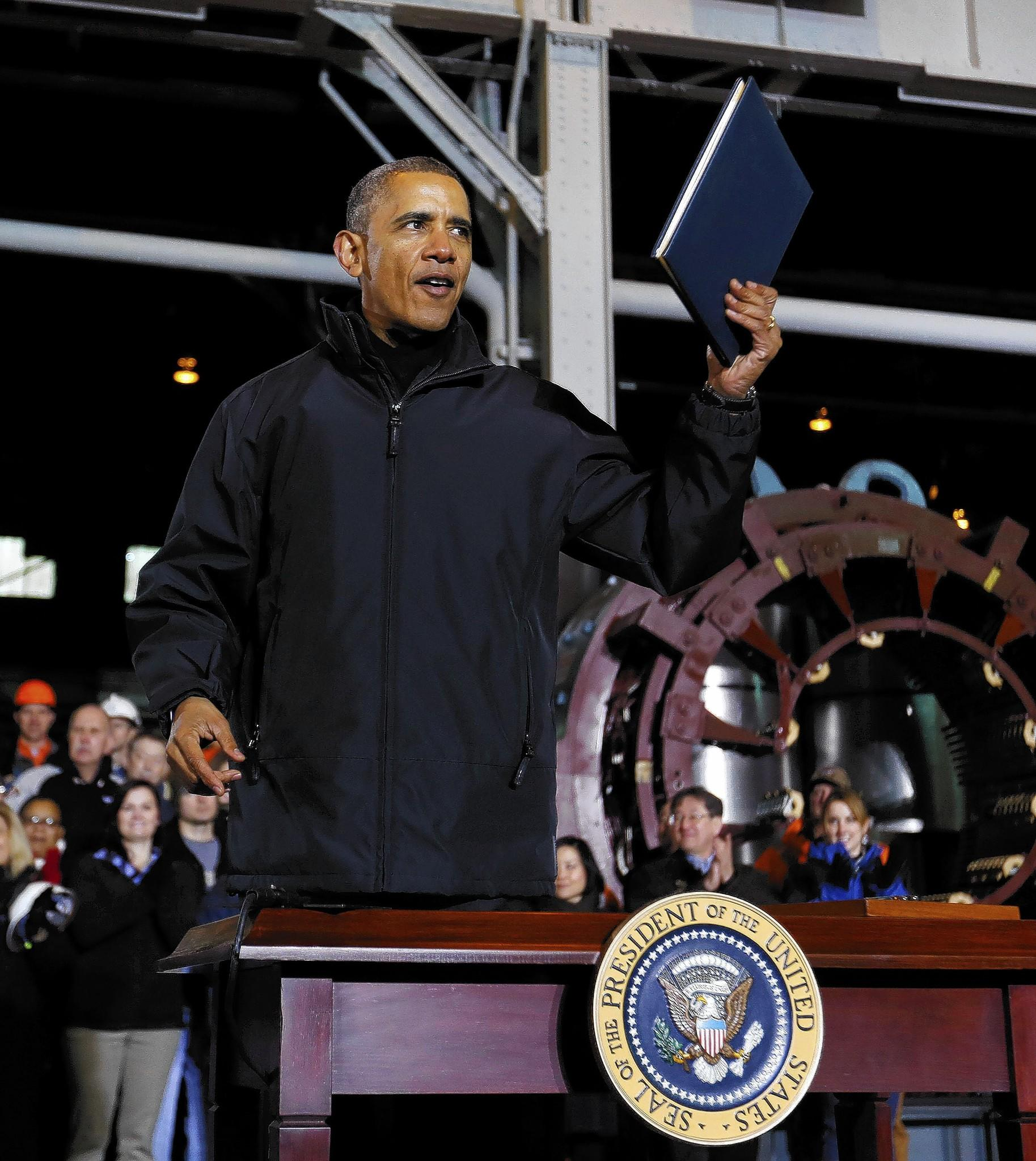 President Obama holds up memorandum instructing U.S. Treasury Department to create a new retirement account system after touring the U.S. Steel Irvin Plant in West Mifflin.