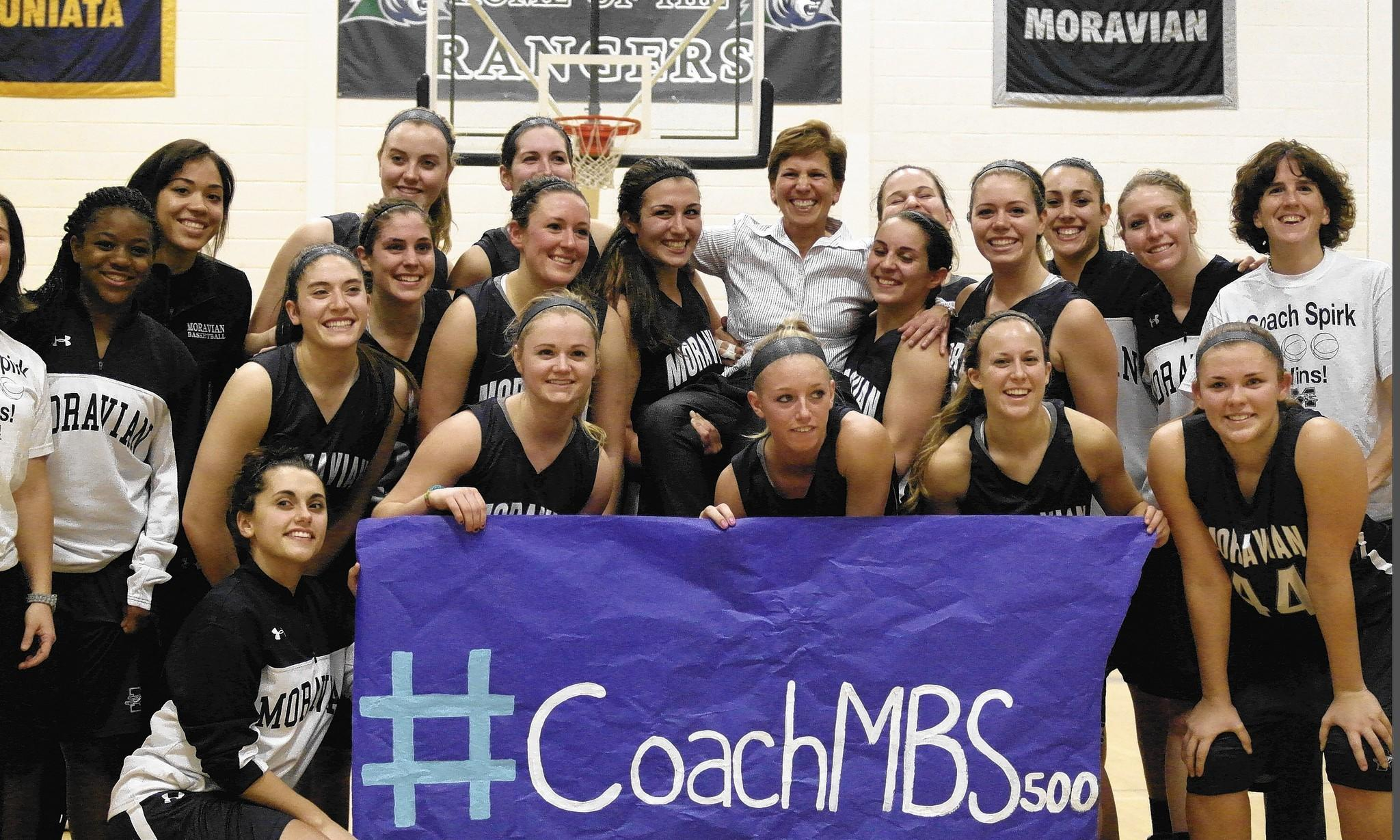 Moravian women's basketball coach Mary Beth Spirk (center with white shirt) celebrates her 500th coaching win with her players.