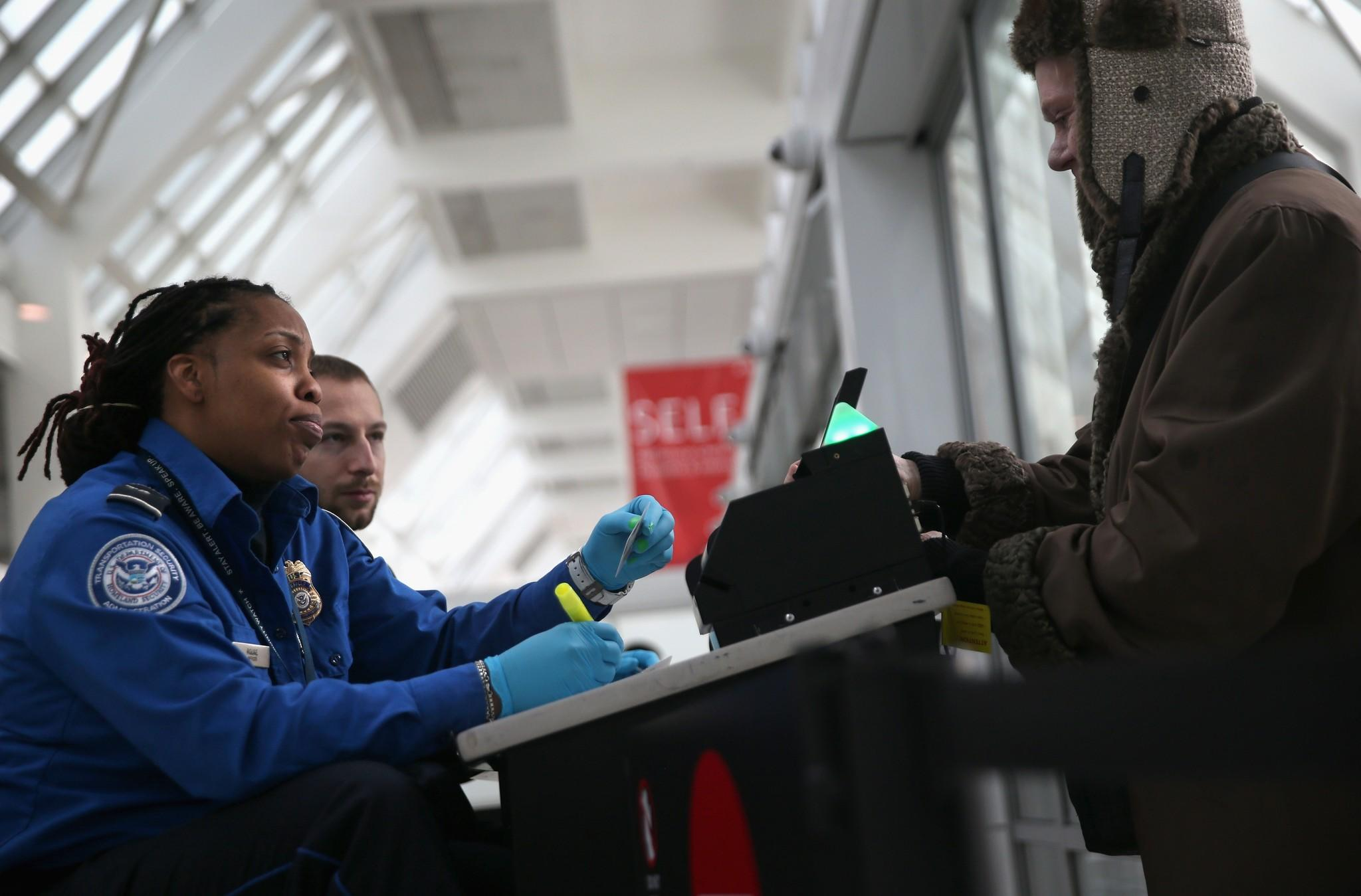 A TSA agent checks a traveler's identification at a special TSA Pre-check lane LaGuardia Airport in New York
