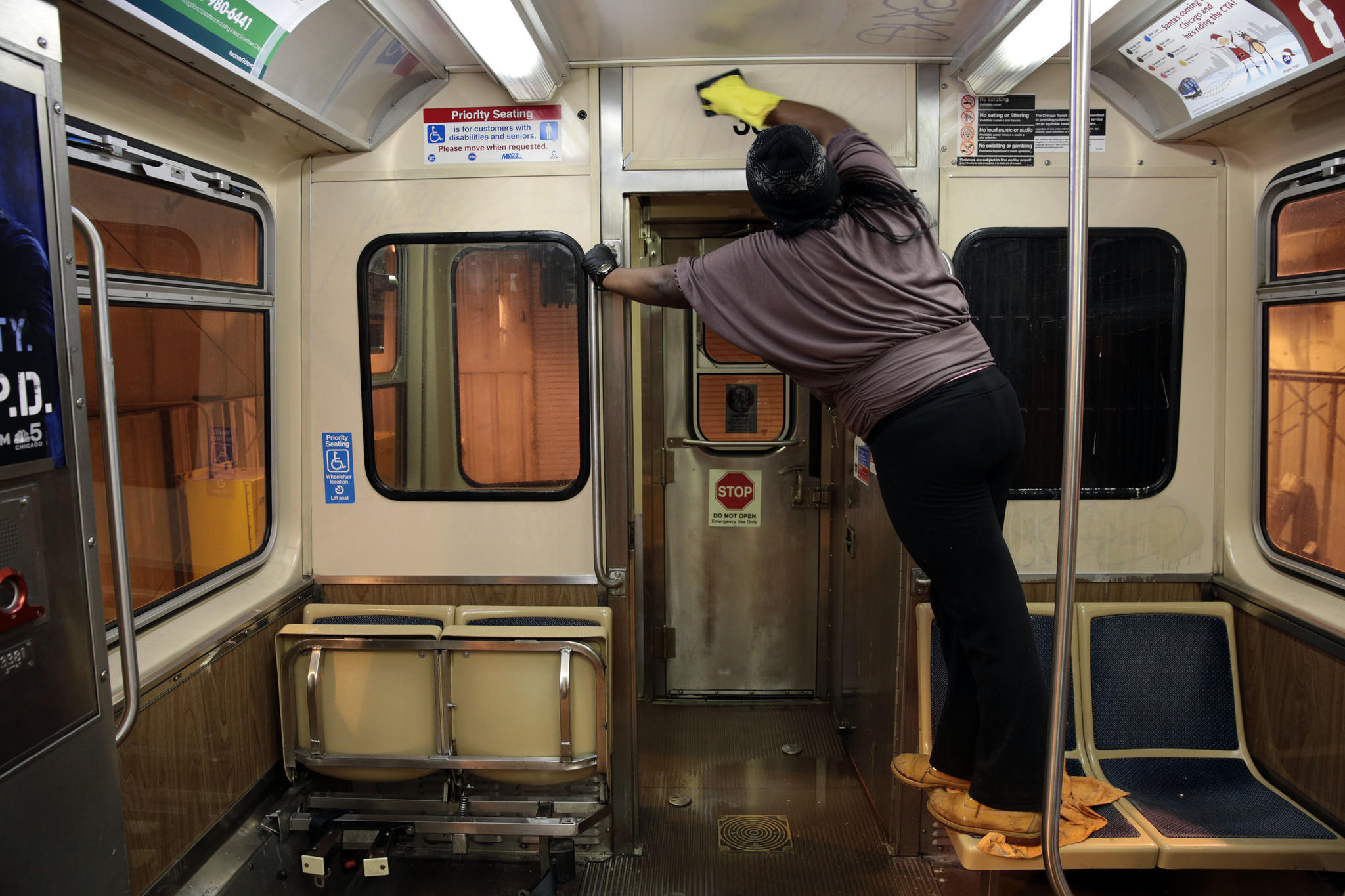 A CTA apprentice cleans a rail car.