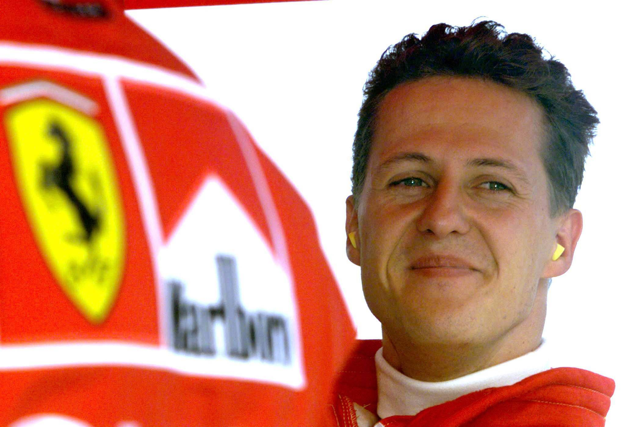 Germany's Michael Schumacher smiles in the pit area after completing his second qualifying session of the Hungarian Formula One Grand Prix in this August 15, 1998 file photo. Ferrari fans held a vigil for Michael Schumacher on his 45th birthday on January 3, 2014, gathering outside the French hospital where the seven times world champion continued to fight for his life after a skiing accident. Schumacher's family thanked the fans in a statement on Friday evening saying they were moved to tears while French media reported that investigators were studying a camera the German had on him at the time of the accident.