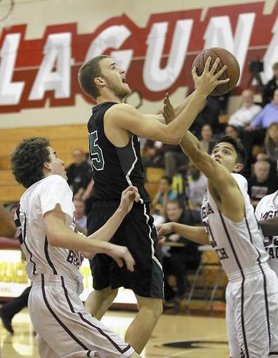 Costa Mesa High's Sean Comer drives to the basket past Laguna Beach's Matt Jones during an Orange Coast League game on Wednesday.