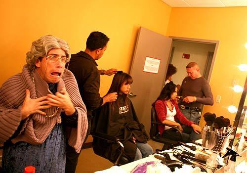 "Adonis Losada, left, gets into character as La Abuelita, or the Little Grandmother, backstage before the taping of a skit on Sbado Gigante. The backstage scene is sometimes as wild as what happens on stage. Young men dressing up in drag  la Tim Conway from the old ""Carol Burnett Show"" can give the impression that one has entered a television time warp."