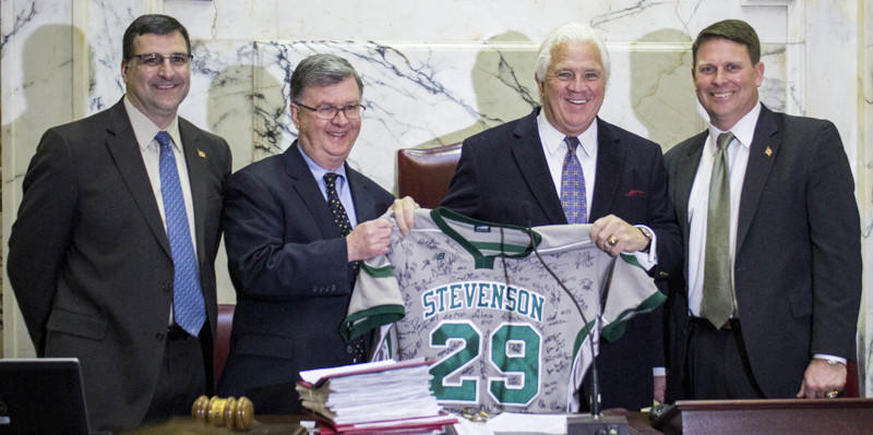 "Division III men's lacrosse national champion Stevenson was honored at the State House on Thursday. (Left to right) Stevenson AD Brett Adams, school president Kevin J. Manning, Senate President Thomas V. ""Mike"" Miller Jr. and Mustangs coach Paul Cantabene pose with a jersey signed by players on the team."