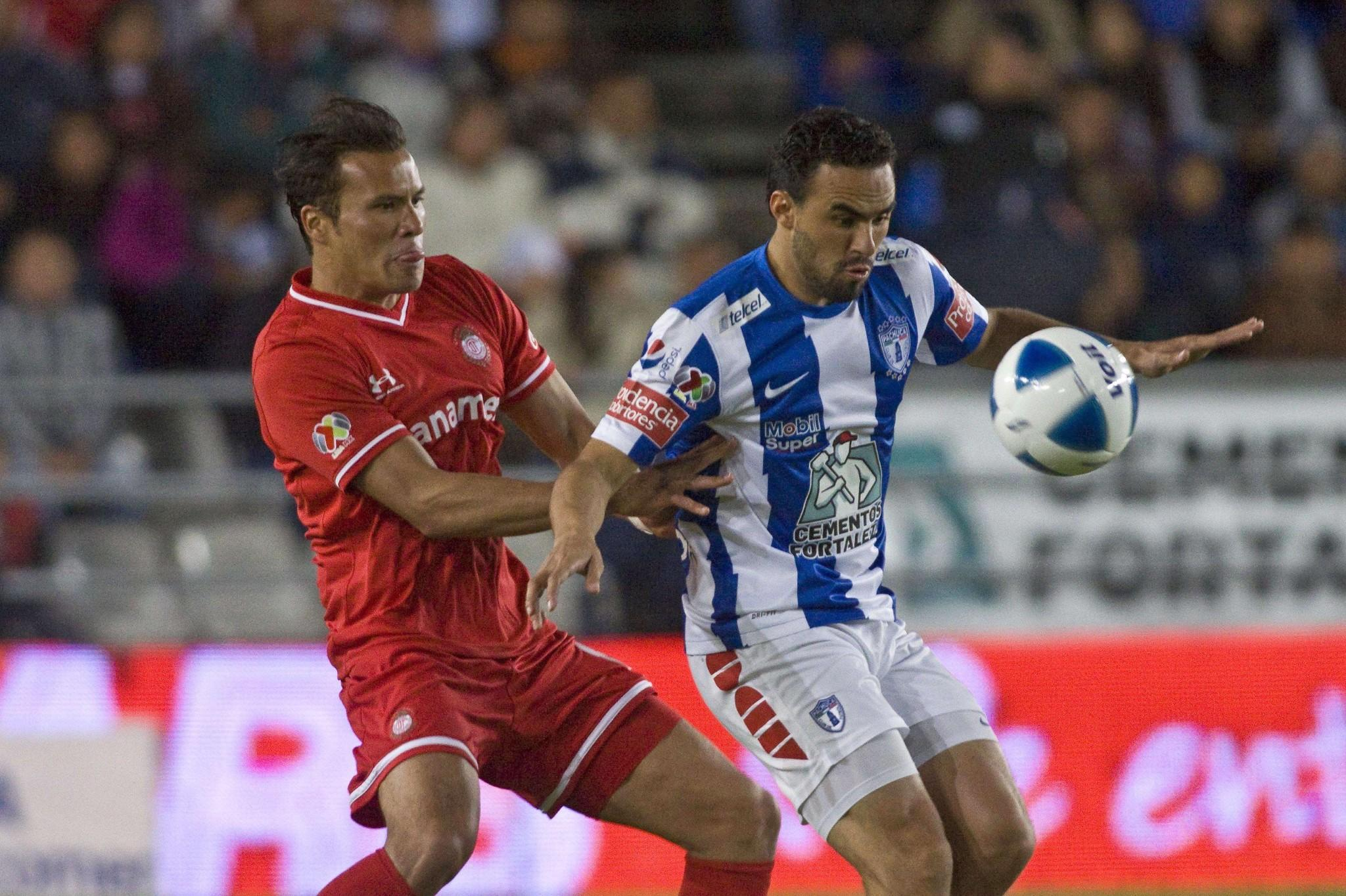 Enrique Esqueda (R) of Pachuca vies for the ball with Aaron Galindo (L) of Toluca during their Mexican Soccer Clausura 2014 tournament in Pachuca, State of Hidalgo, Mexico, on January 04, 2014.