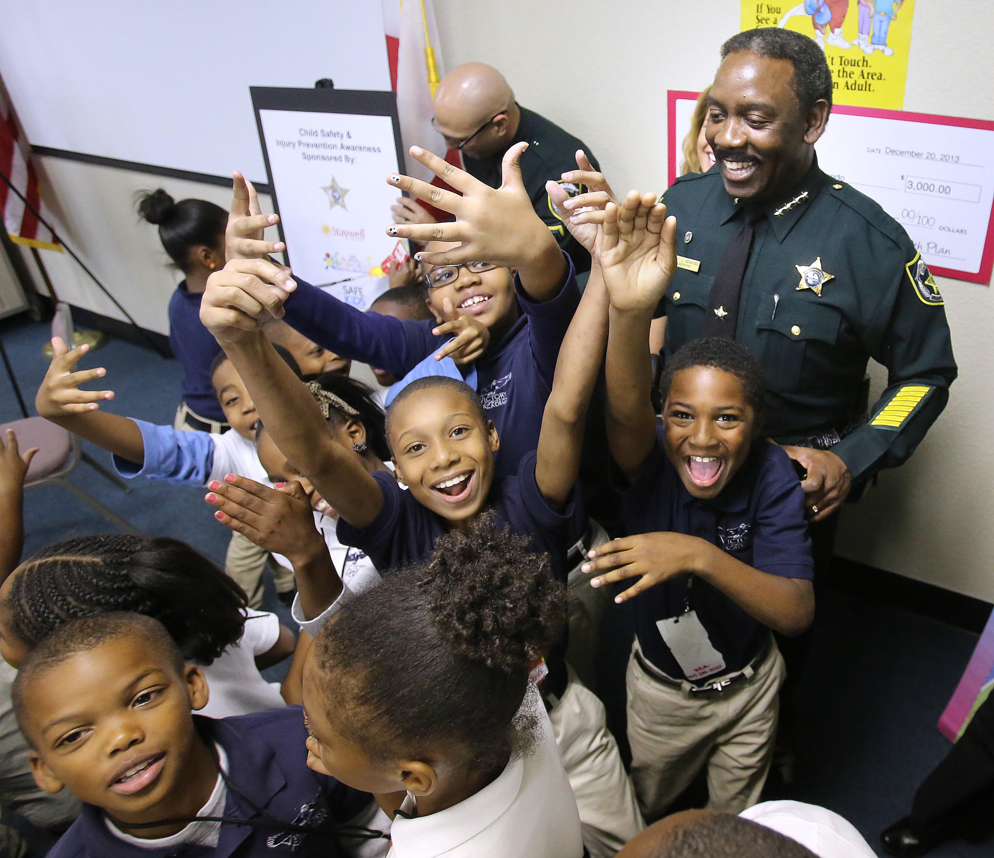 Students from Victory Christian Academy of Orlando joke with Orange County Sheriff Jerry Demings during the announcement for the Project ChildSafe program in Orlando, Thursday, Jan. 29, 2014.