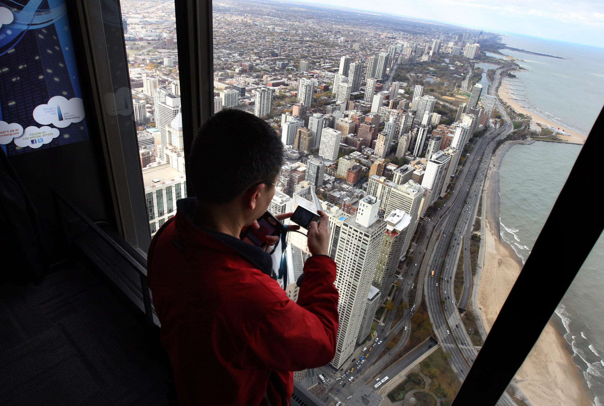 A tourist aims his camera out the window towards the north side of the city at the John Hancock observatory.