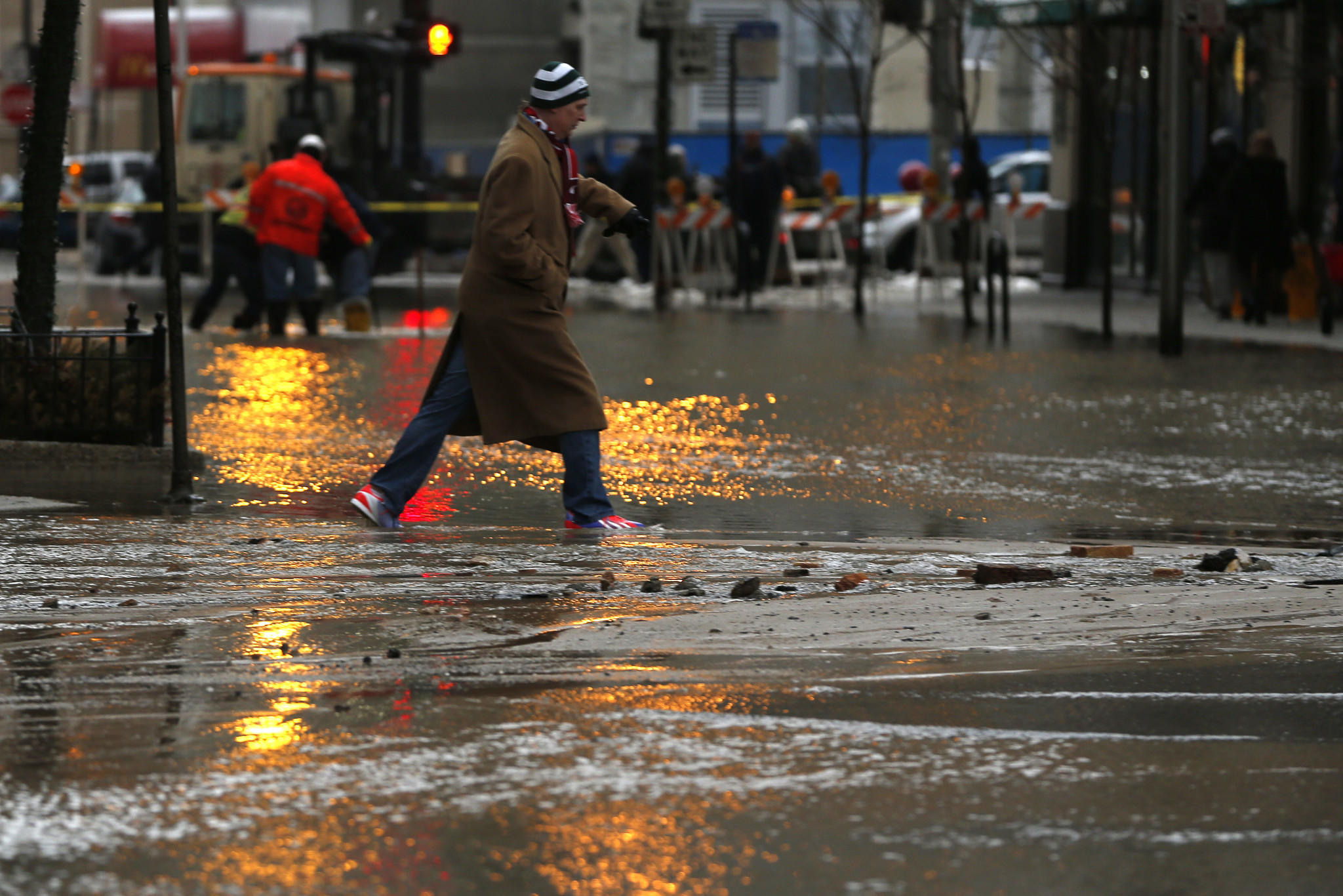 A pedestrian navigates a water main break at Ohio Street and McClurg Court in Chicago.