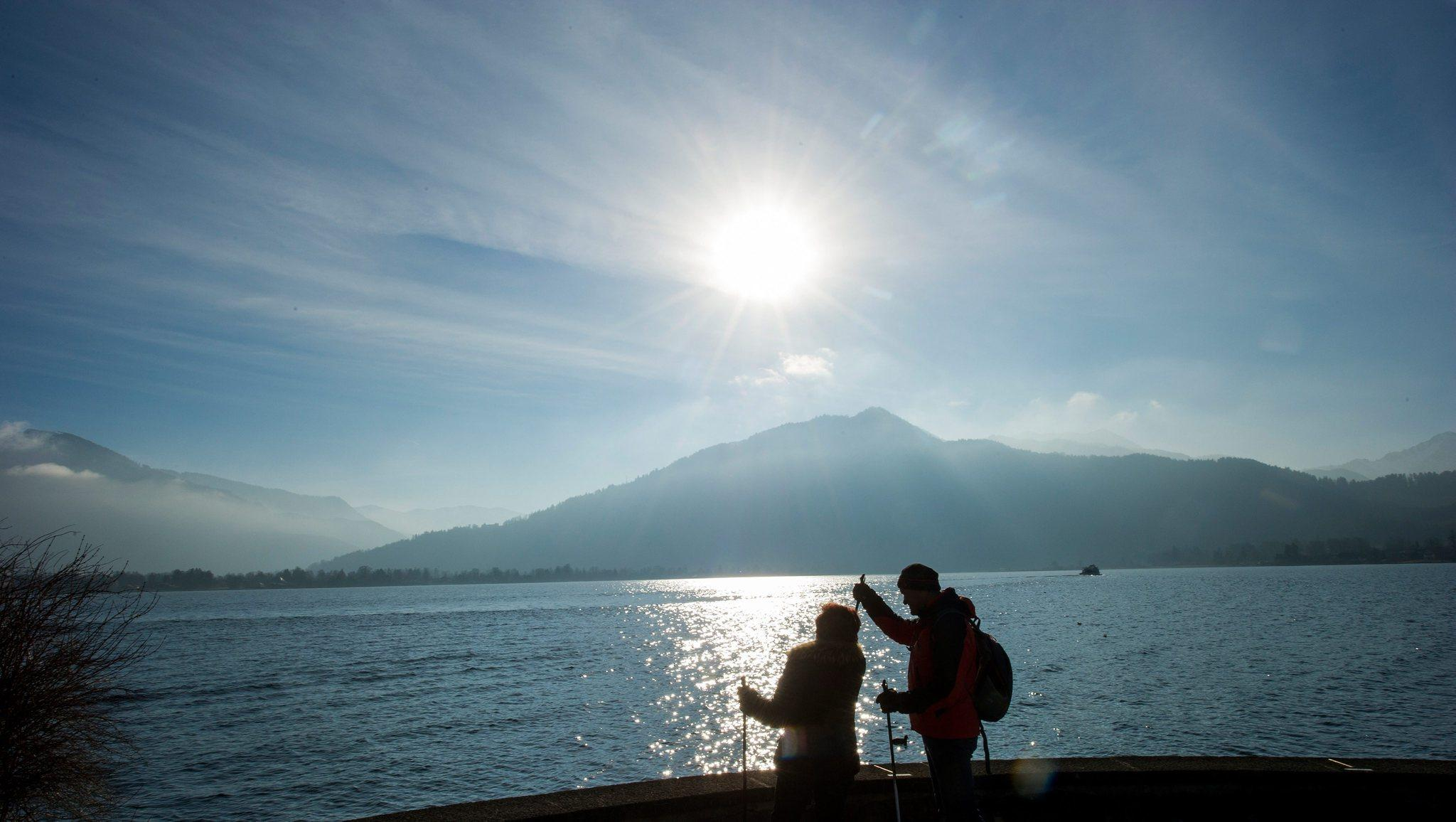 Hikers look at the mountains on the banks of Tegernsee lake in Tegernsee, Germany, 12 January 2014.
