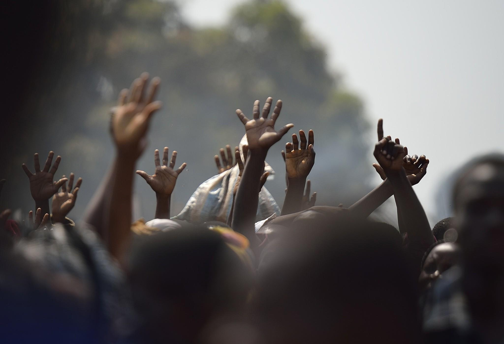 Displaced people raise their hands as they wait for food distribution in central Africa.