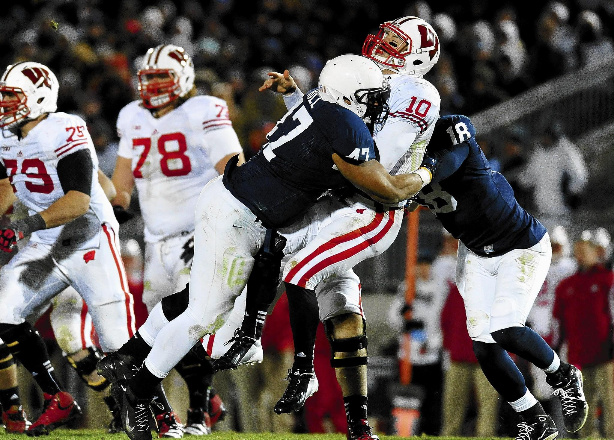 November 24, 2012; University Park, PA, USA; Wisconsin Badgers quarterback Curt Phillips (10) is hit by Penn State Nittany Lions defensive tackle Jordan Hill (47) at Beaver Stadium.