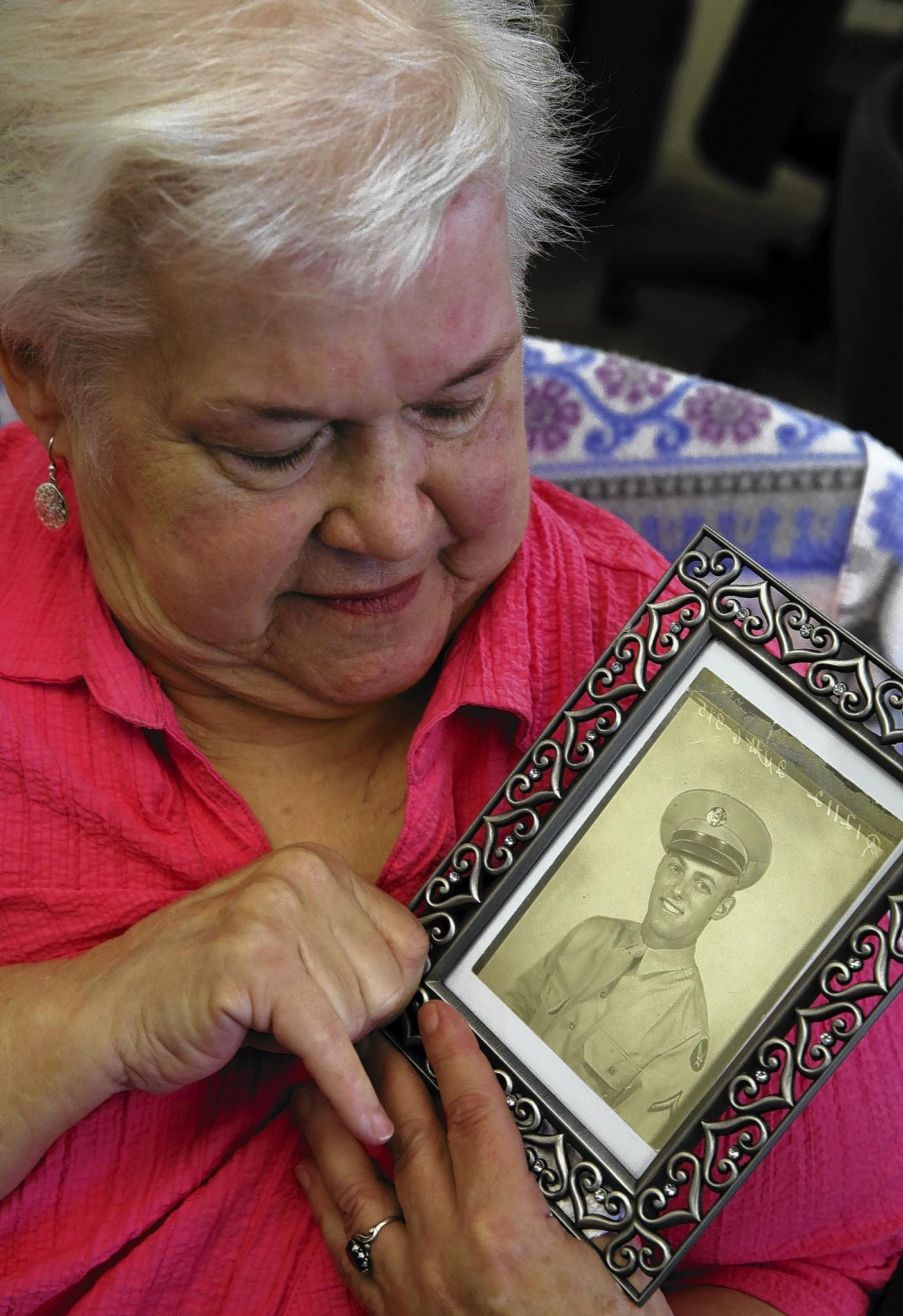 Sharon Mangerson, holds up a photo of her step father, John Wrana, following a press conference Sept. 16, 2013, where she spoke of her step father John Wrana, a 95 yr. old who died after being hit with a Taser and shot with bean bag ammunition by Park Forest police.