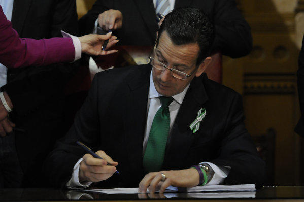 Gov. Dannel P. Malloy signs a historic gun control bill into law.