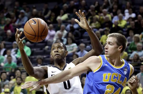 UCLA forward Travis Wear (24) and Oregon forward Mike Moser (0) battle for a rebound in the first half Thursday night in Eugene.