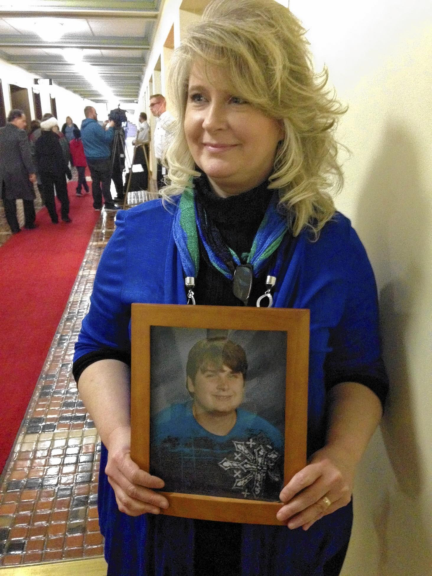 Deena Kenney of Bethlehem holds a picture of her son, Chris, who suffers from epilepsy. She testified Tuesday in Harrisburg at a legislative hearing on a bill to allow medical marijuana in Pennsylvania.