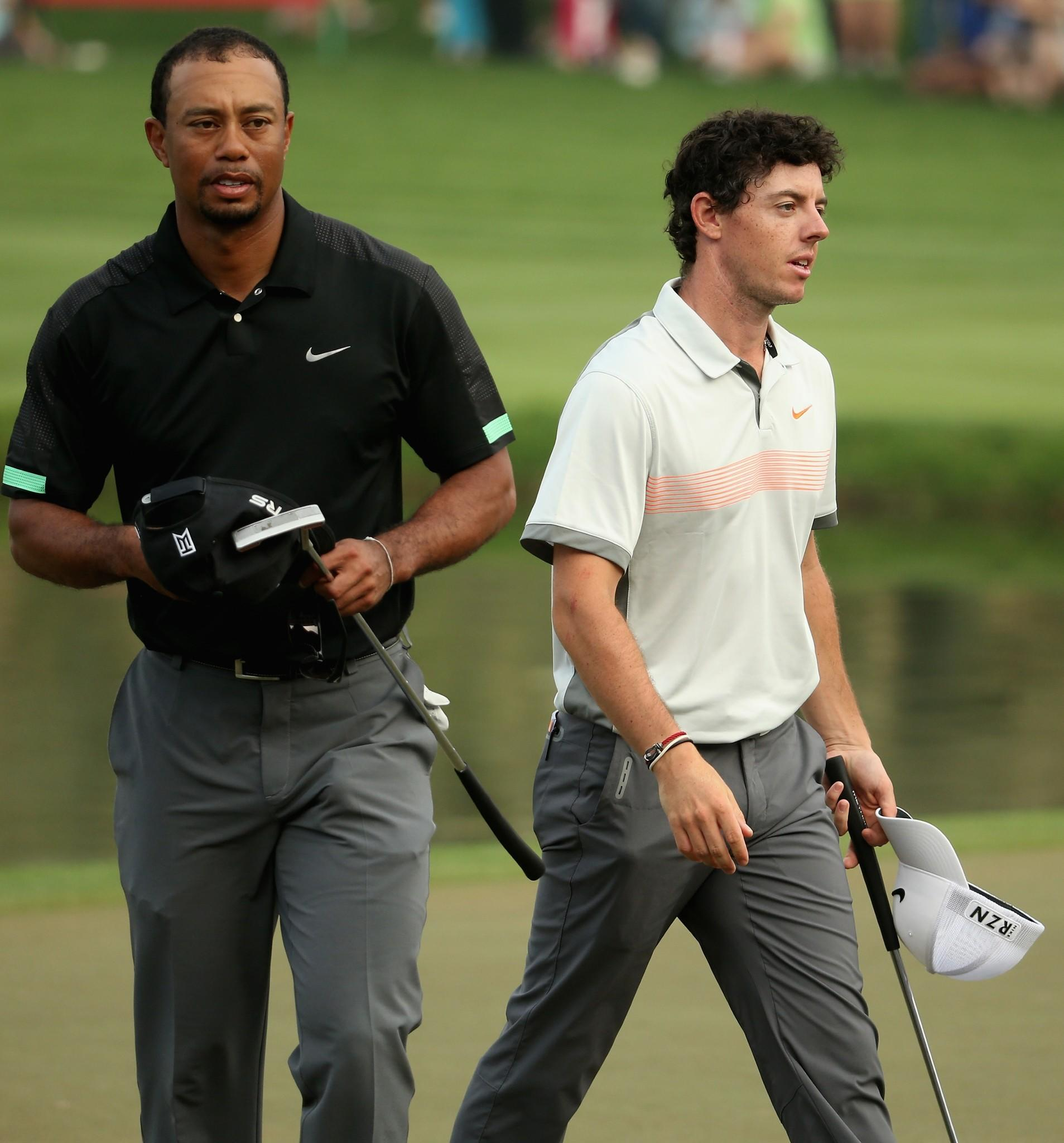 Rory McIlroy and Tiger Woods walk off the 18th green during the second round of the 2014 Omega Dubai Desert Classic Friday.