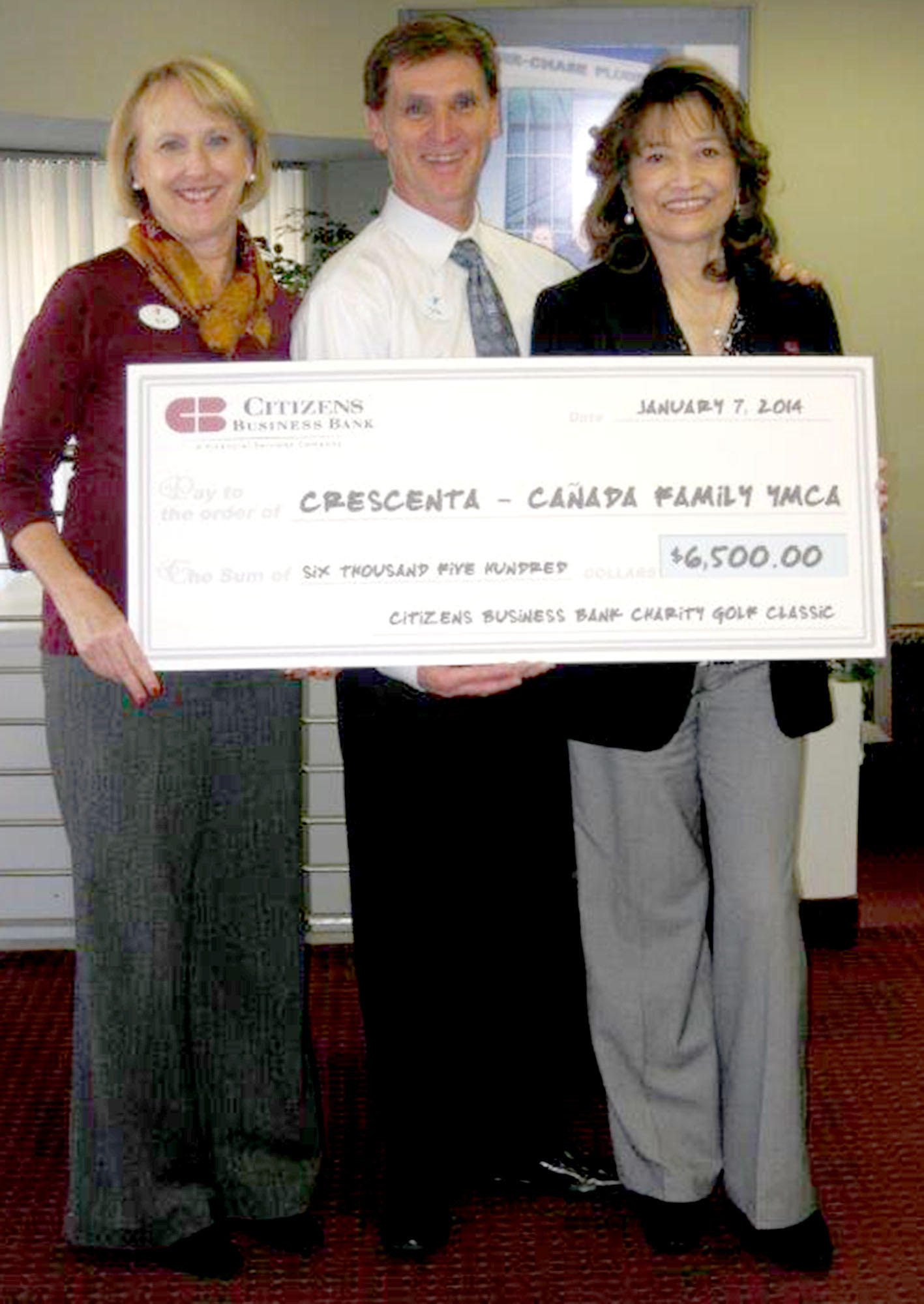 Kim Beattie and Tyler Wright, from left, accept a check made out to the Crescenta-Canada Family YMCA from Emelita S.L. Bituin, vice president and manager of the Citizens Business Bank in La Cañada Flintridge. The $6,500 check represents a portion of the funds raised during the 2nd Annual Region 3 Citizens Business Bank Charity Golf Classic held in October at Oakmont Country Club. Proceeds are distributed to local nonprofits.