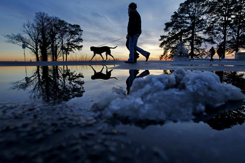 Patrik and Camilla Lasson walk their dog Roxy as snow piles melt while the sun sets Friday evening near Lions Bridge.