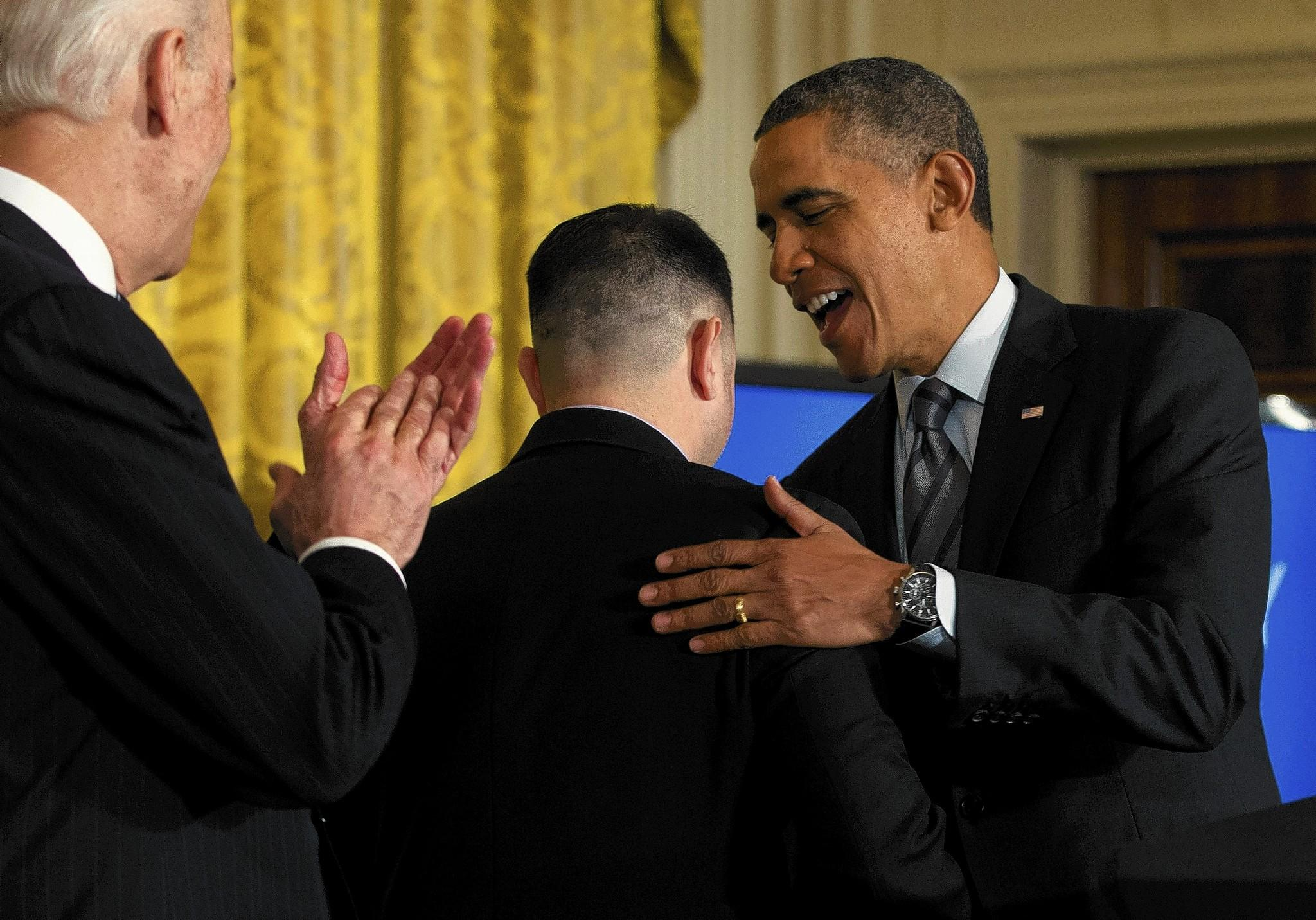 At the White House, President Obama talks with PG&E apprentice electrician Erick Varela, center, a former U.S. Army combat infantryman in Iraq, as Vice President Joe Biden, left, applauds before Obama spoke about helping the long-term unemployed.