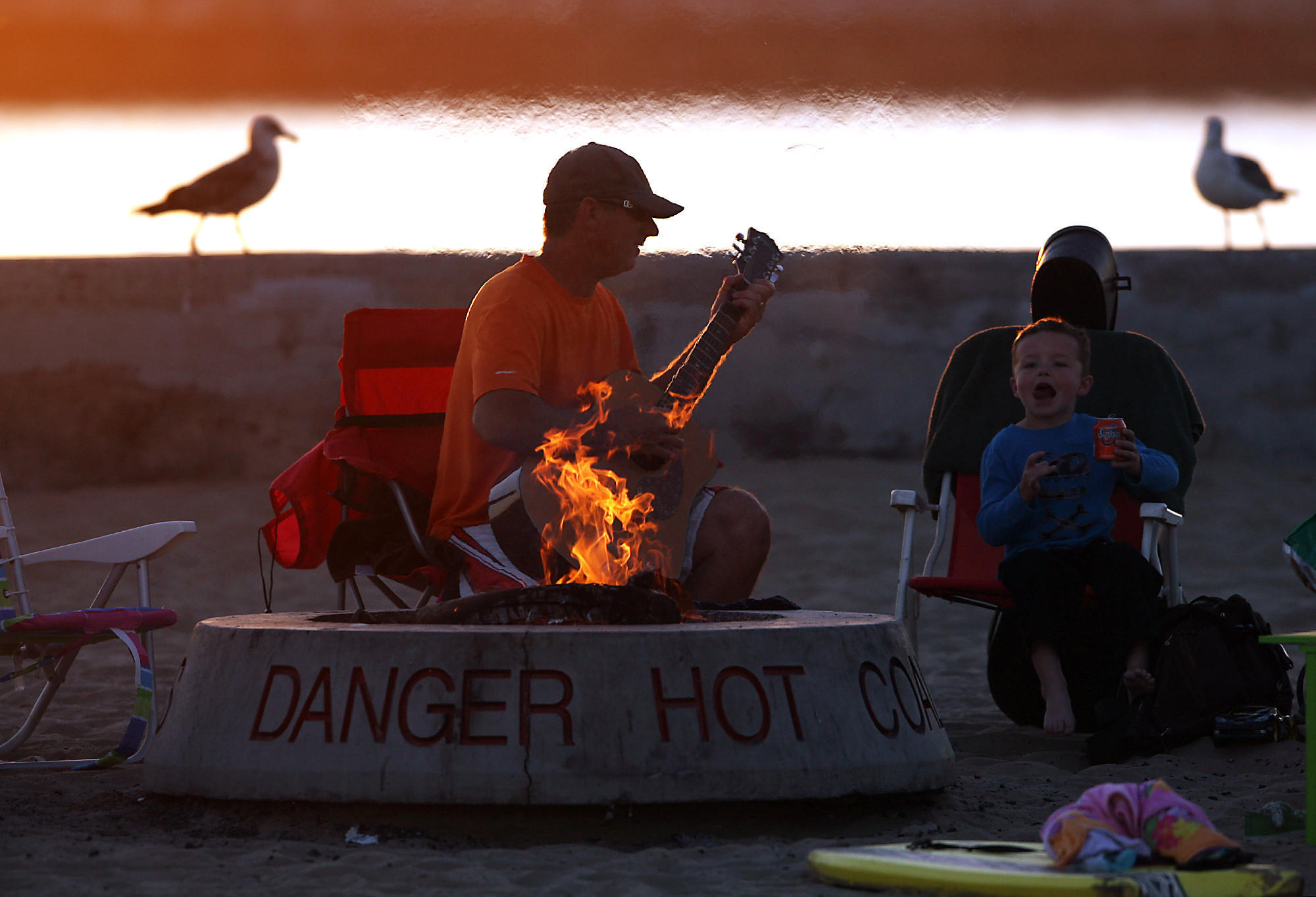 Dave Osinga and his son Zachary sit by the fire as the sun sets at Corona del Mar State Beach.