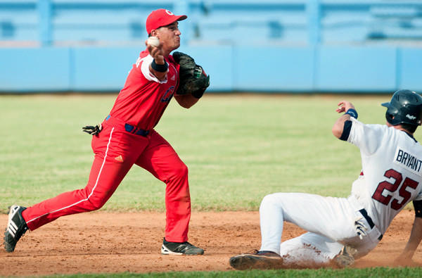 Cuba infielder Alexander Guerrero relays a throw to first base on a double-play attempt against the U.S. during an exhibition game.