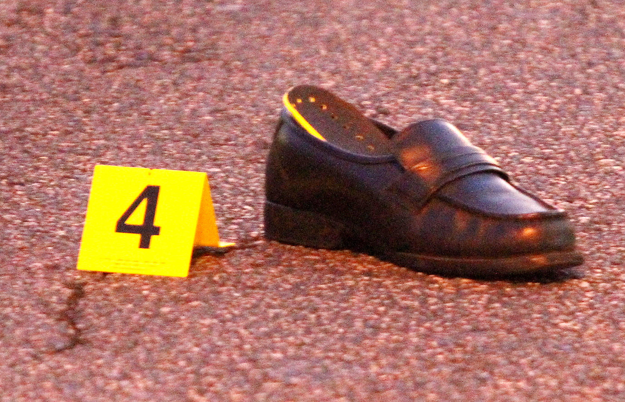 A shoe, tagged as evidence, on the street at the scene where a pedestrian was hit by a motorist on the corner of Glenoaks Blvd. and Western Avenue in Glendale on Monday, January 27, 2014. The pedestrian was taken to the hospital with severe head injuries.