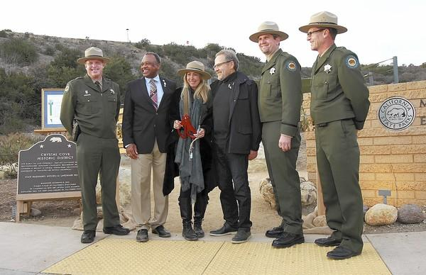 Michael and Tricia Berns, center, stand with California State Parks Director, Major General Anthony Jackson, second from left, and a host of park rangers during Crystal Cove Alliance and California State Parks grand opening of the Berns Environmental Study Loop at Crystal Cove on Friday.