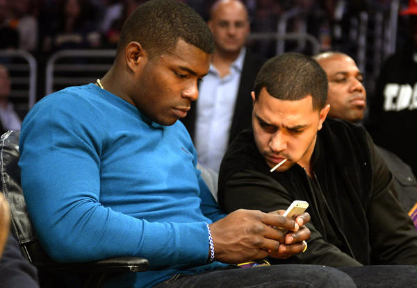 Dodgers outfielder Yasiel Puig checks his phone while attending a Lakers-Pacers game at Staples Center last week.