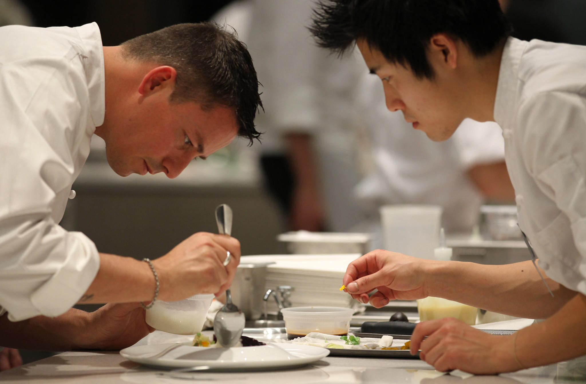 Chef Curtis Duffy and sous chef Dan Bark, decorate a plate at Grace restaurant.
