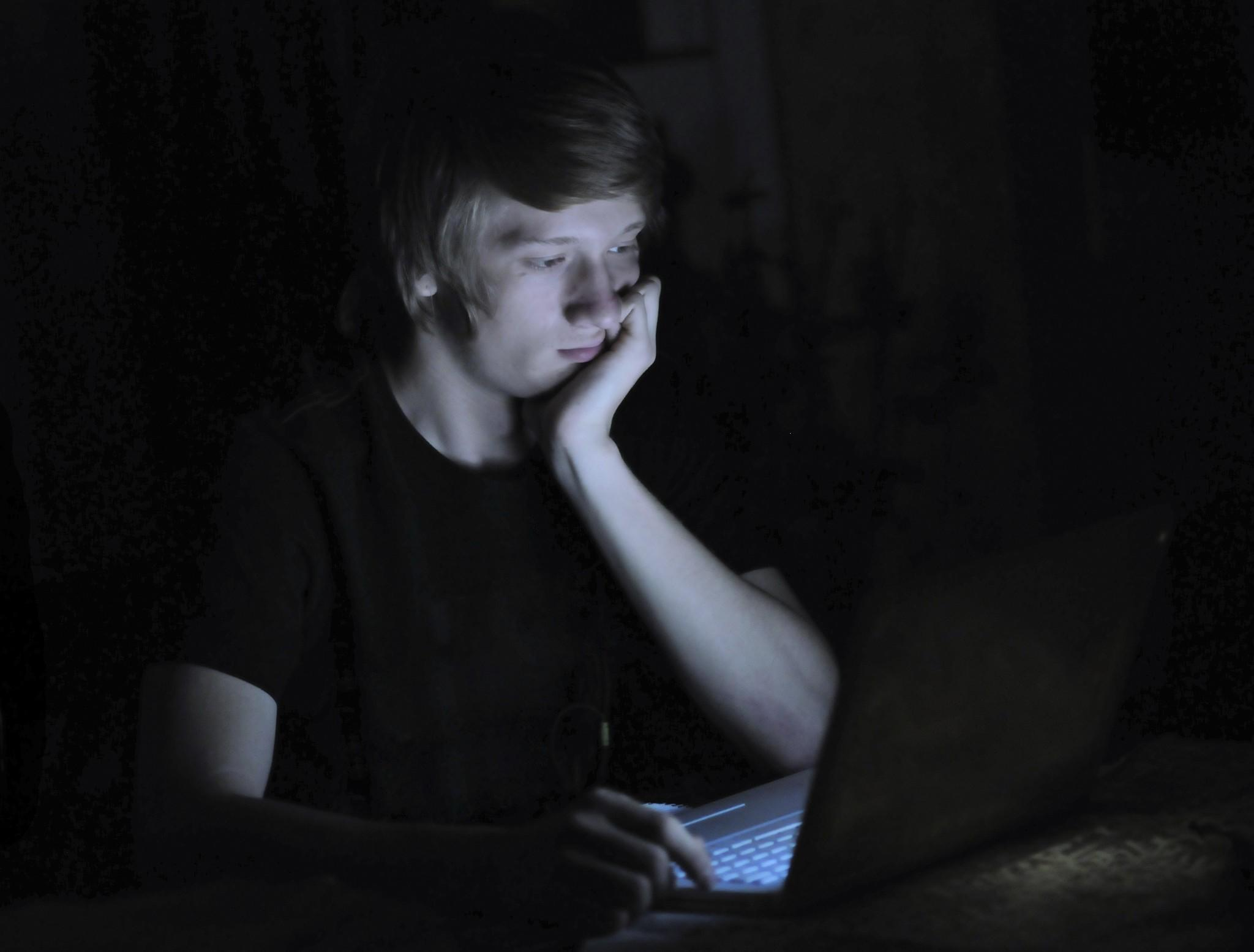 Teenage Male on Computer Laptop Late at Night. Stock photo from Getty Images.