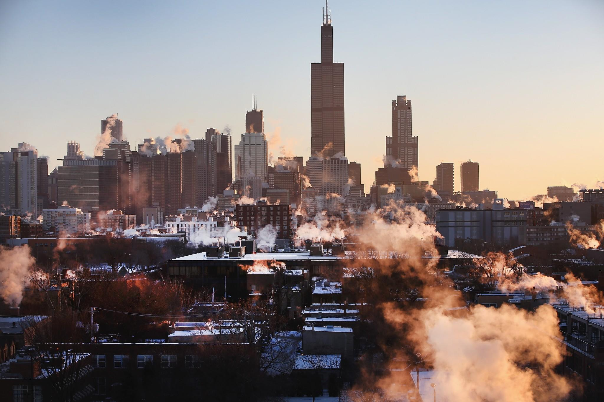 The sun rises behind the Chicago skyline.