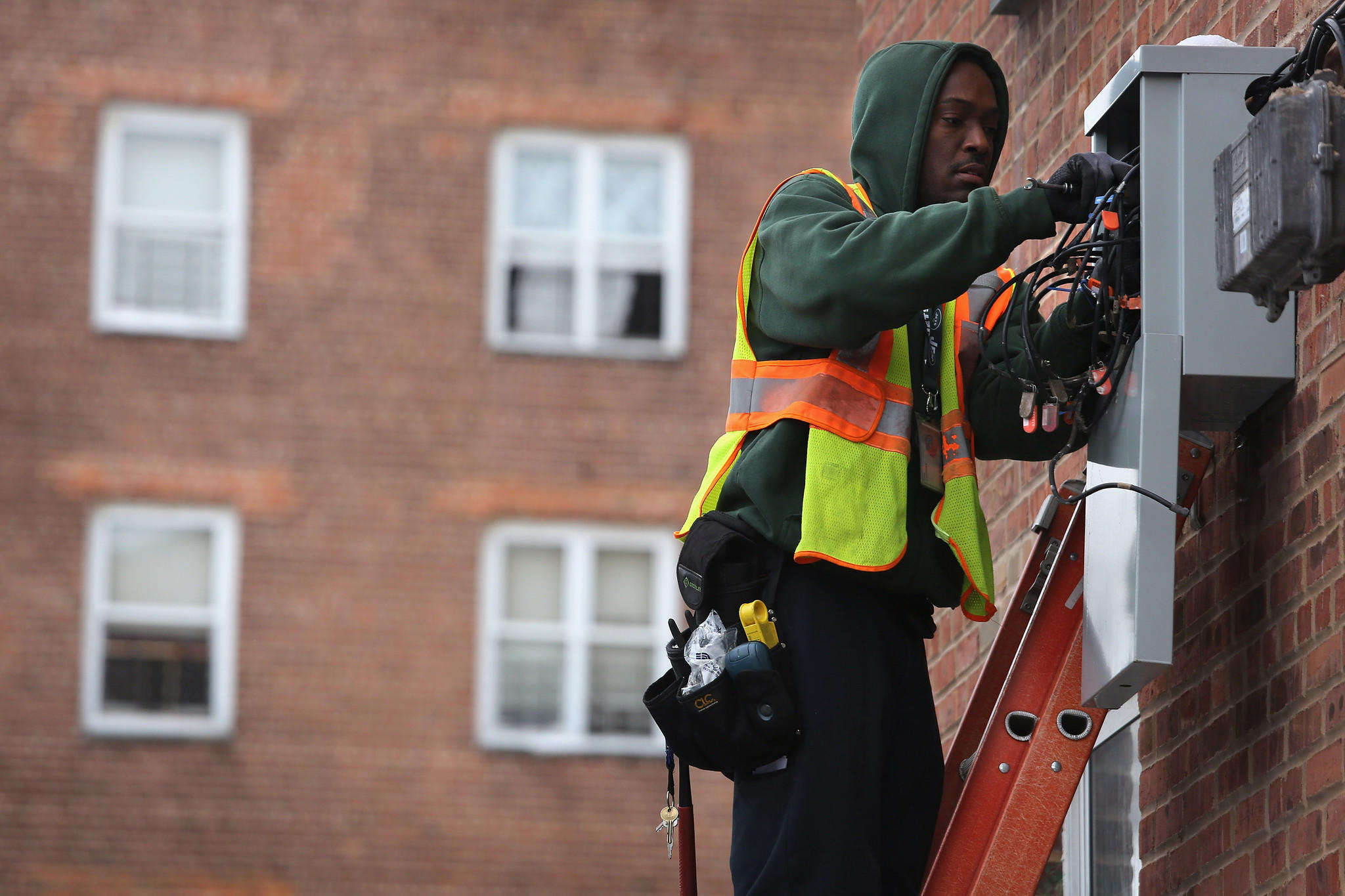 A worker for Time Warner Cable works to restore television reception to an apartment building.