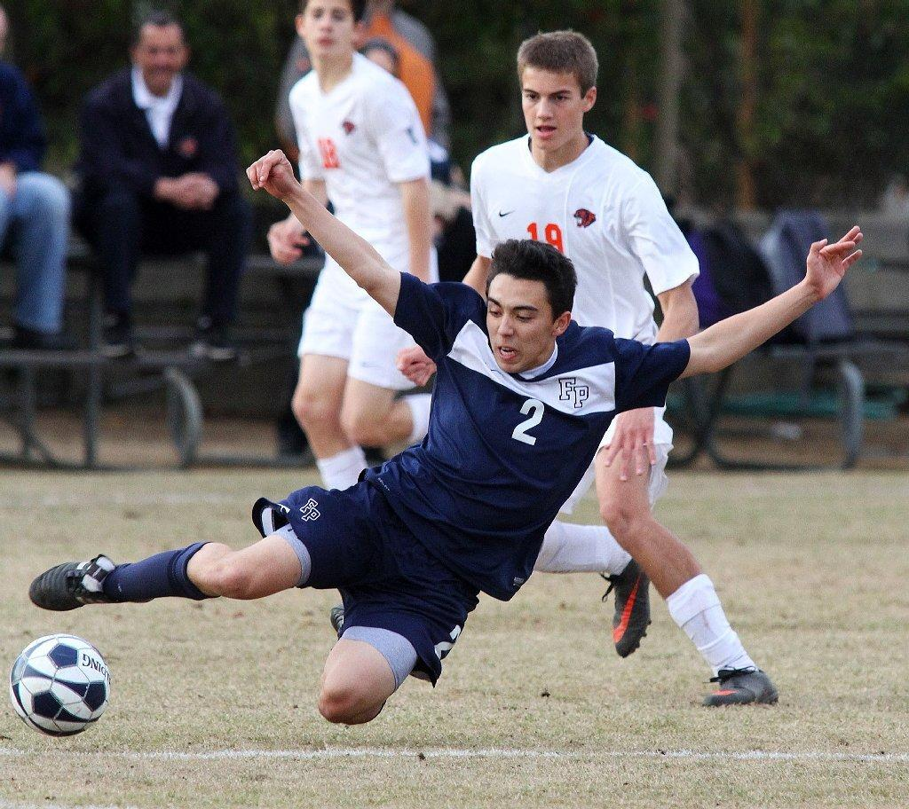 Flintridge Prep's Daniel Enzminger falls to the ground kicking the ball against Pasadena Poly in a Prep League boys' soccer game at Poly on Friday. The Rebels lost, 3-2. (Tim Berger/Staff Photographer)