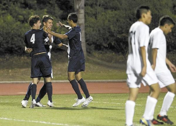Corona del Mar High's John O'Connor, left, and Blake Munger, right, congratulate Kyle Martin after he scored a goal against Irvine.