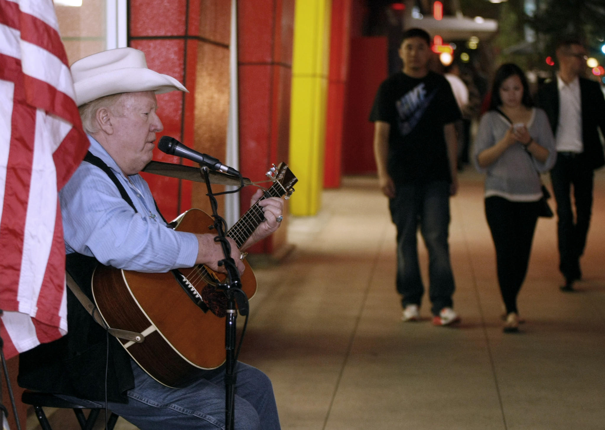 Street performer Red Benson plays folk rock on Brand Blvd. as people walk by, in Glendale on Saturday, January 25, 2014. Benson has been playing at this location for about 15 years.