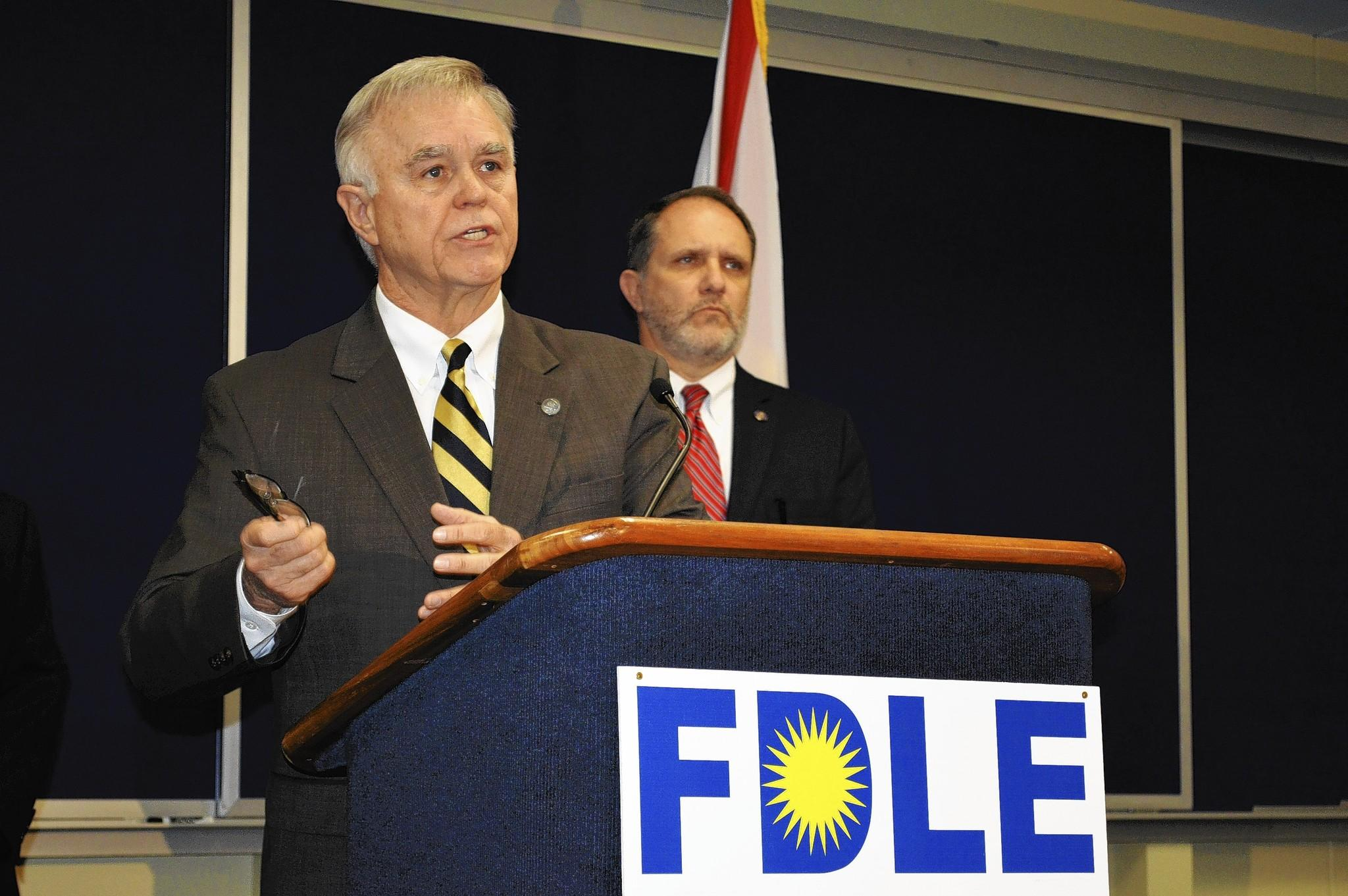 Florida Department of Law Enforcement Commissioner Gerald Bailey, with Assistant FDLE Commissioner Jim Madden (R), announces an investigation into evidence tampering that could affect hundreds of drug cases handled by a chemist in the Pensacola FDLE laboratory.
