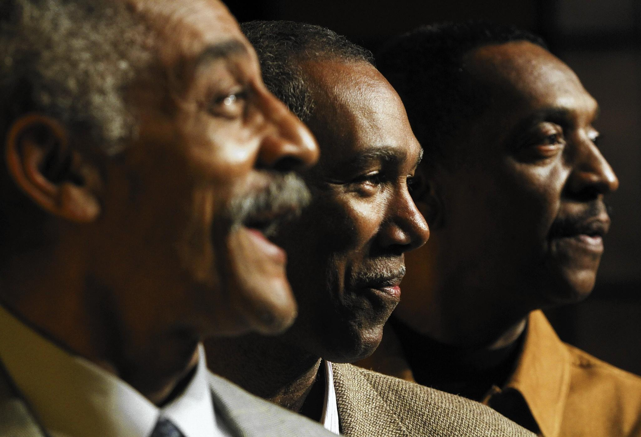 The Unifics, Tom Fauntleroy, Garrett Hall and Charlie Lockhart, pose for a portrait in the Ella Fitzgerald Theater at the Downing-Gross Cultural Arts Center in Newport News. The members of the vocal harmony group say they will continue to make music in tribute to their late friend and colleague, Al Johnson.